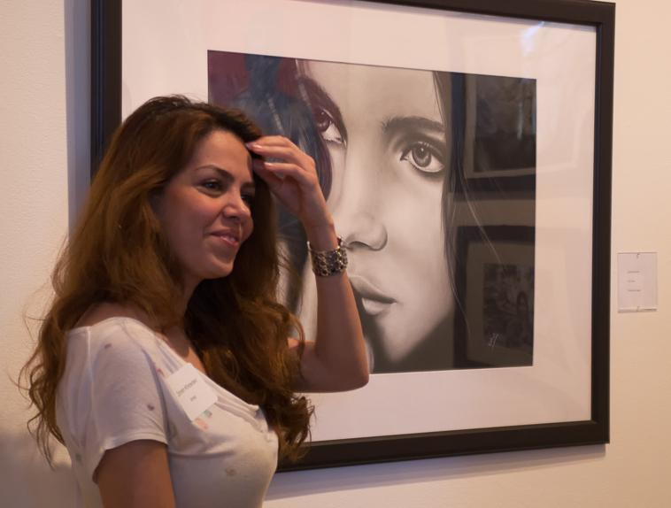 Artist's Creation Zohren Khosravi stands by her charcoal drawing, a replica of a photograph.