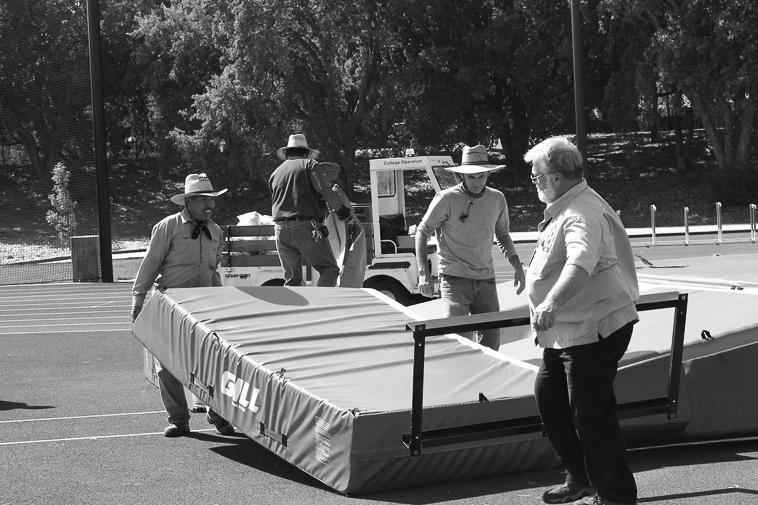 Joe Cook, far right, and Reyes Hernandez, far left, move mats near De Anza's athletics track.