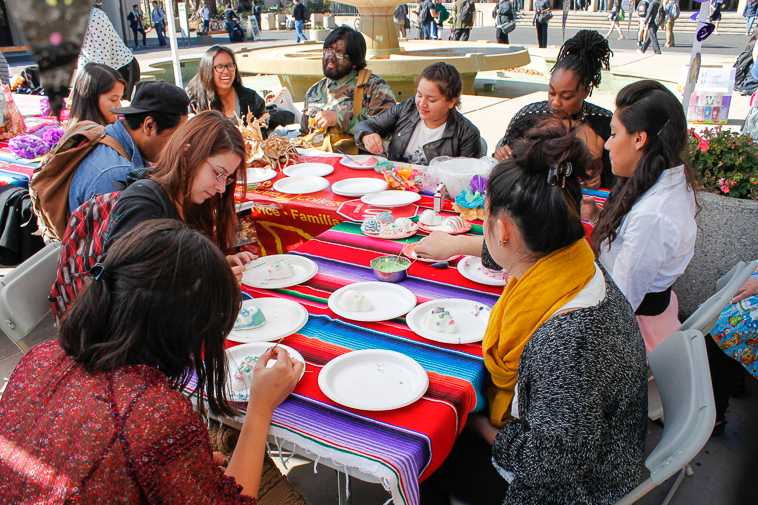 Tables filled with students eager to paint sugar skulls during the Dia de los Muertos celebration.