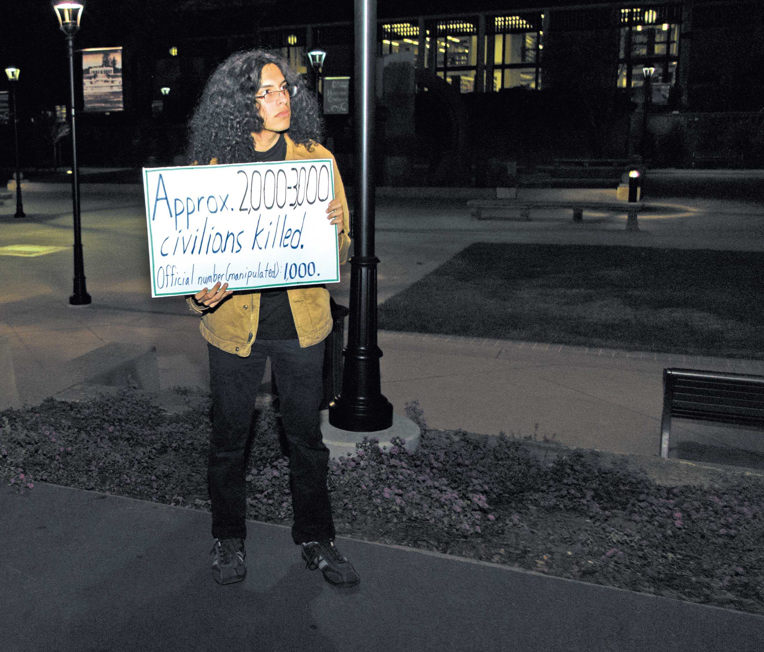 Students for Justice club member Steven Alvarado holds up a sign detailing the number of civilian drone strike casualties in protest of former Secretary of Defense Leon Panetta, who spoke at the Flint Center at De Anza College, Feb. 20.