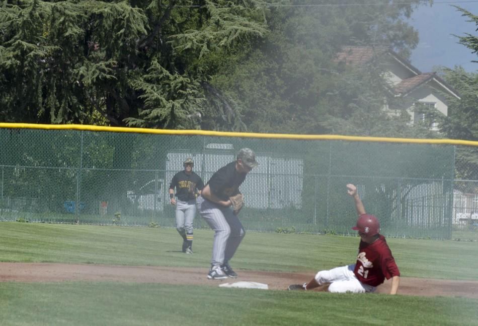 Freshman outfielder Christopher O'Conner (21) attempts to slide into second base before the Chabot shortstop tries to tag the base on April 10.