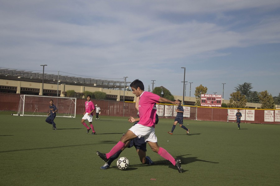 Wearing pink for National Breast Cancer Awareness month, De Anza freshman midfielder Roy Ortiz (2) goes in for a tackle against a West Valley defender.