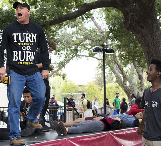 Students lie down on the stage in the main quad at De Anza College to block preacher Mark Trout, on Thursday, May 21.