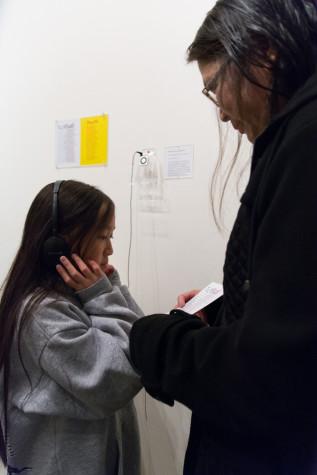 "Grace Tringh (left) and Karen Wong (right) listen to ""Ong Do,"" a musical piece by artist Phillip Hua."
