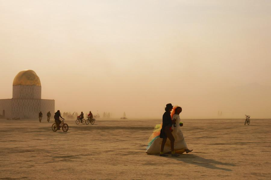 """A couple dressed as bride and groom walk away from the Library of Babel at Burning Man 2014. Photo """"Lost in the Dust """"won first place at the JACC Northern California conference in the Features Photo category, on Saturday Nov. 7."""