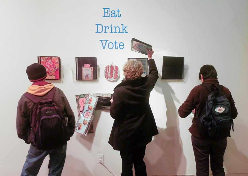 "Guests inspect work created by professor Eugene Rodriguez's photography students, entitled ""Eat Drink Vote Love."""