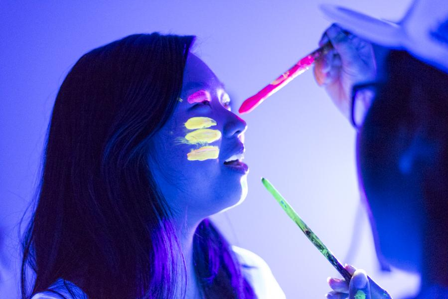 A student has her face painted at the Neon dance xx date