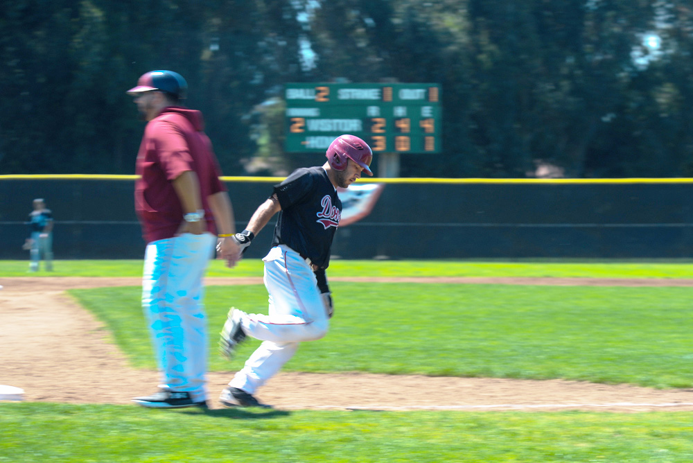 """Catcher Ro Mahanty high-fives third base coach Brian """"Boomer"""" Richer  as he rounds the bases following his home run in a 9-7 victory against Skyline College on April 20, at Baylands field."""