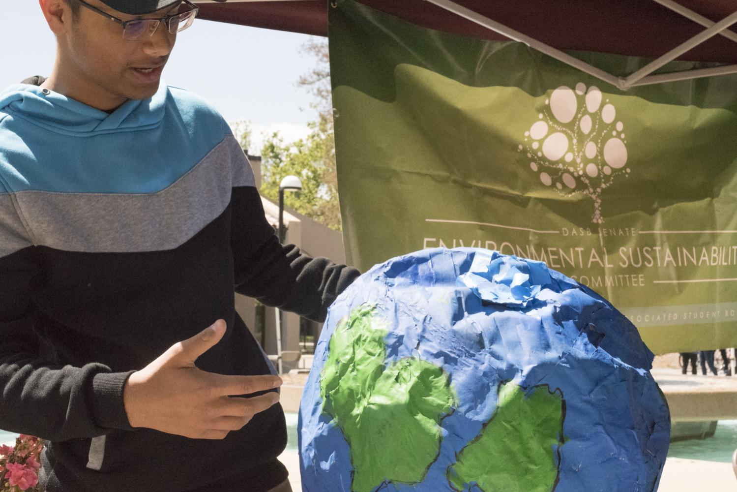 Adita Vishwakarma, 18, engineering major, explains the importance of environmental sustainability on a paper-mache globe made out of old La Voz issues