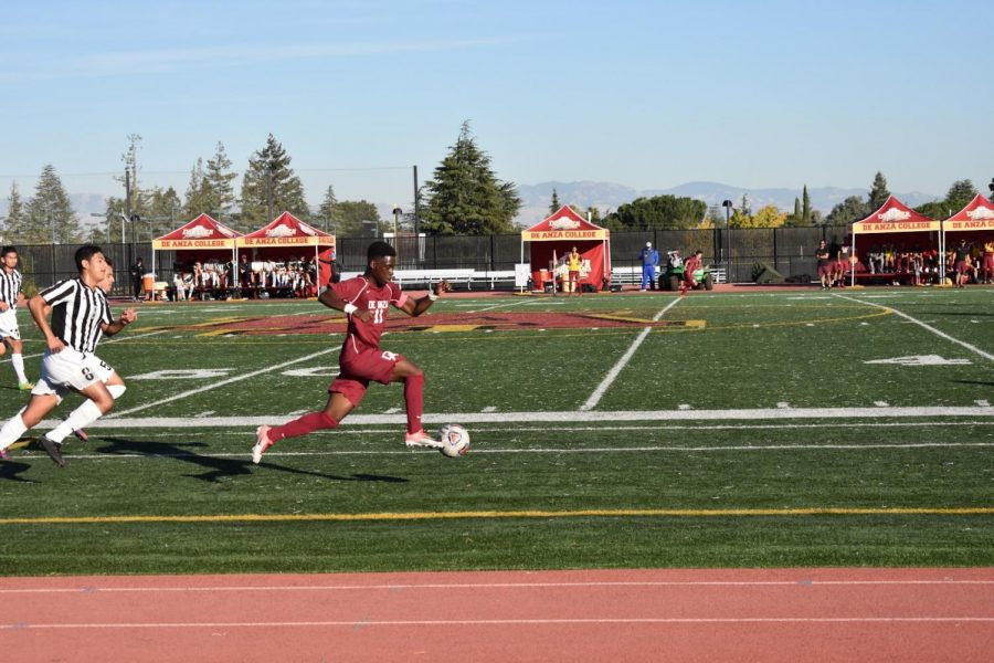 De Anza forward Sahr Mattia dribbles the ball into the Evergreen half of the field while pursued by Evergreen defenders. The Dons won, 2-1.