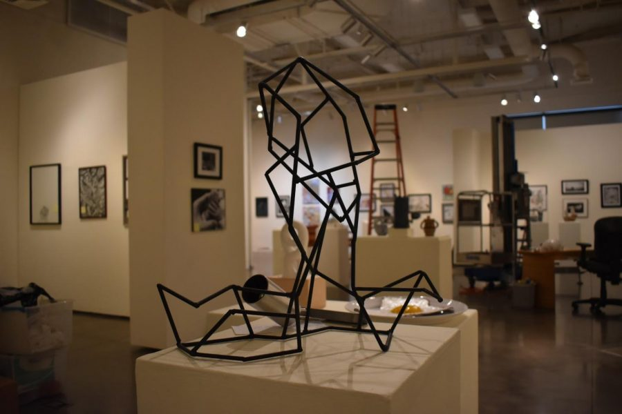 Art pieces stand scattered apart from each other as the lightening for the exhibit is set up.