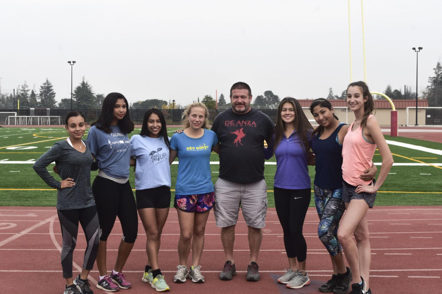 The women's cross country team poses together with their coach.