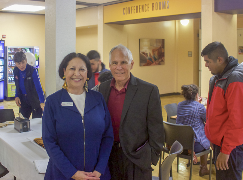 Chancellor Judy Miner and district trustee Peter Landsberger stand in front of the Chancellor's open office hour welcome table in the dining center on Nov. 28.
