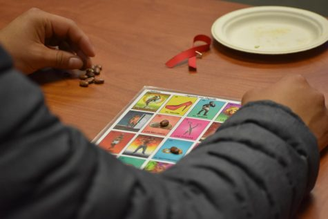 Aldo Martinez, 23, art major, plays the game Joteria, and LGBTQ+ version of Loteria during the event.