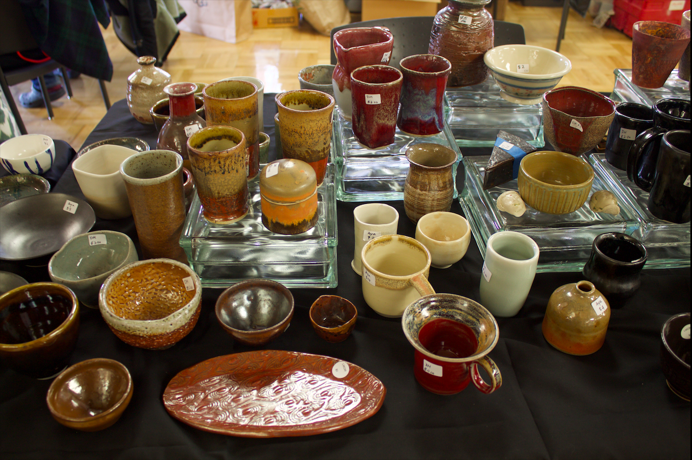 An assortment of handmade cups line the ceramics table in the Campus Center on Dec. 5.