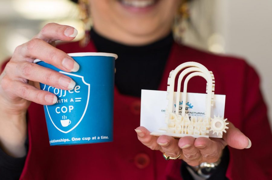 Foothill-De Anza Chancellor Judy Miner holds up a cup of coffee and a 3D printed De Anza College logo.