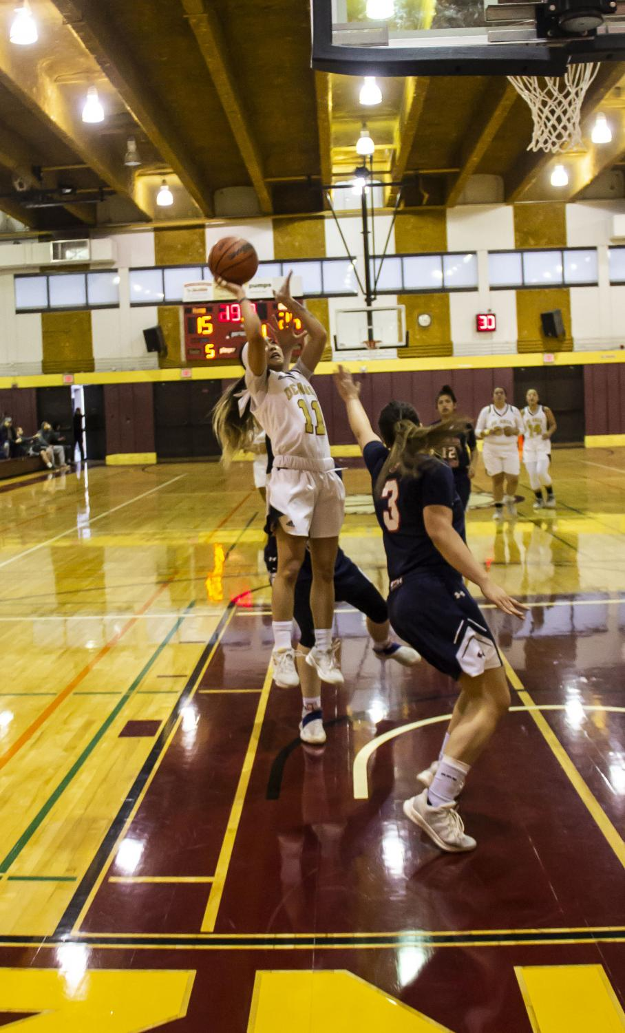 Guard Doryn Gomex makes a successful shot attempt over an opposing defender during a home game on Feb. 13.