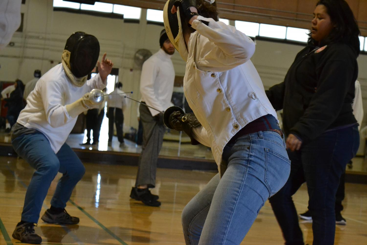 Two masked students face off in a friendly spar during fencing class on March 11.