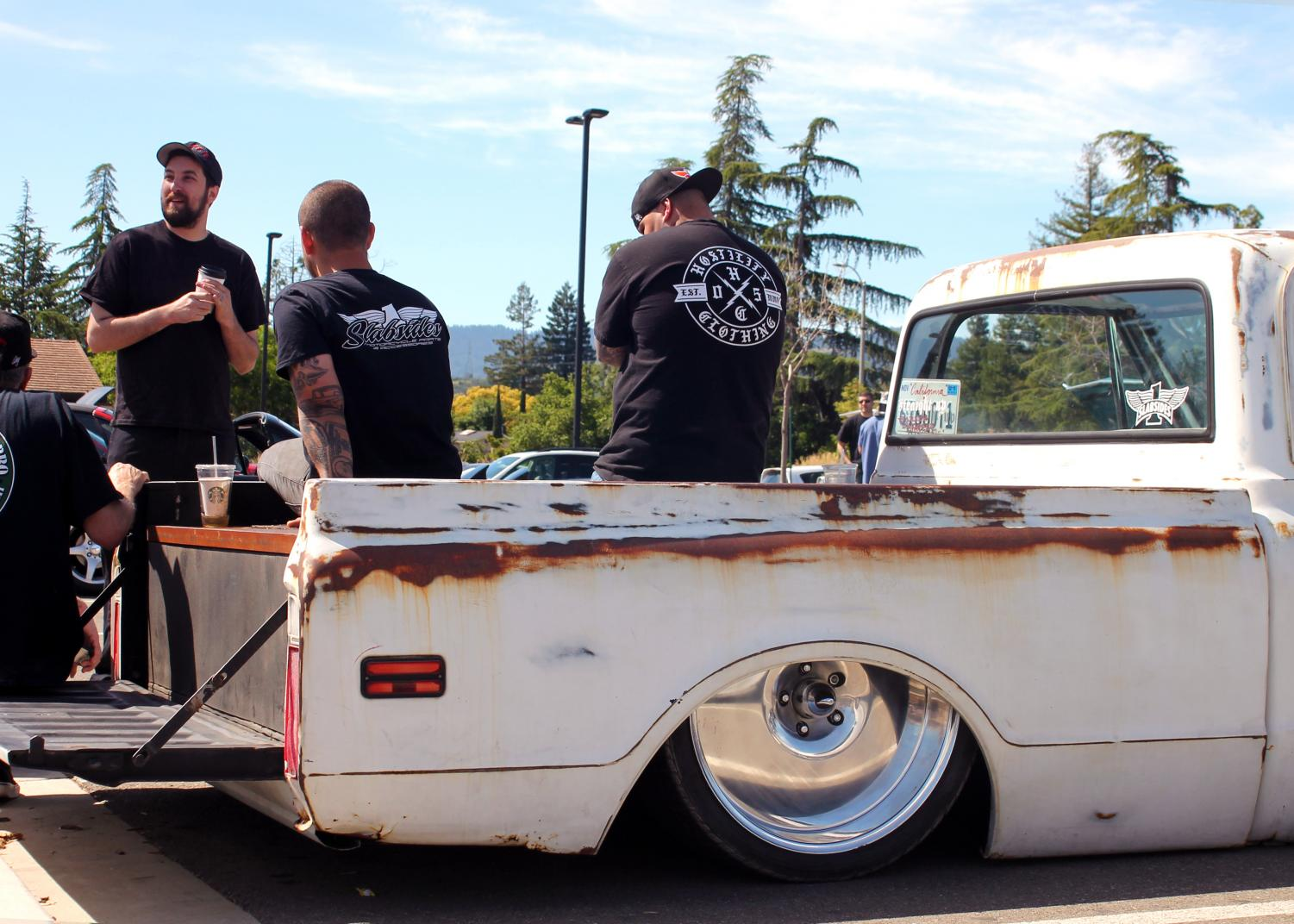 Car+lovers+sit+together+on+their+Chevrolet+C10+pickup+truck+circa+1970s.