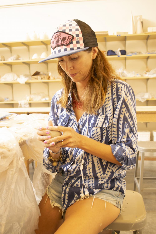 Veronica Felix, 44, ceramics major, molds clay into a soccer ball.