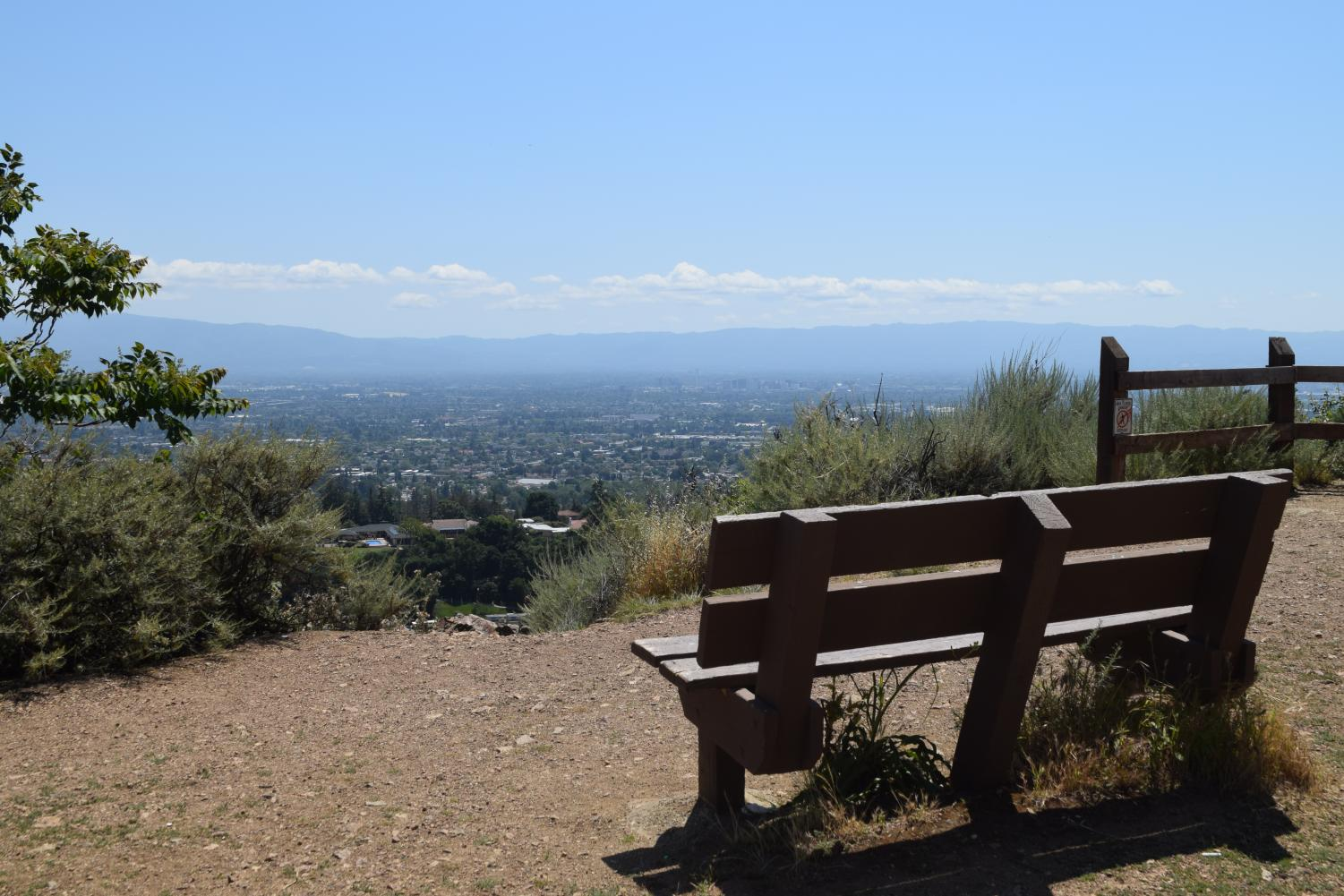 Wooden+bench+at+the+end+of+the+hike+that+overlooks+the+city+of+San+Jose%2C+the+blue+sky+and+mountains.