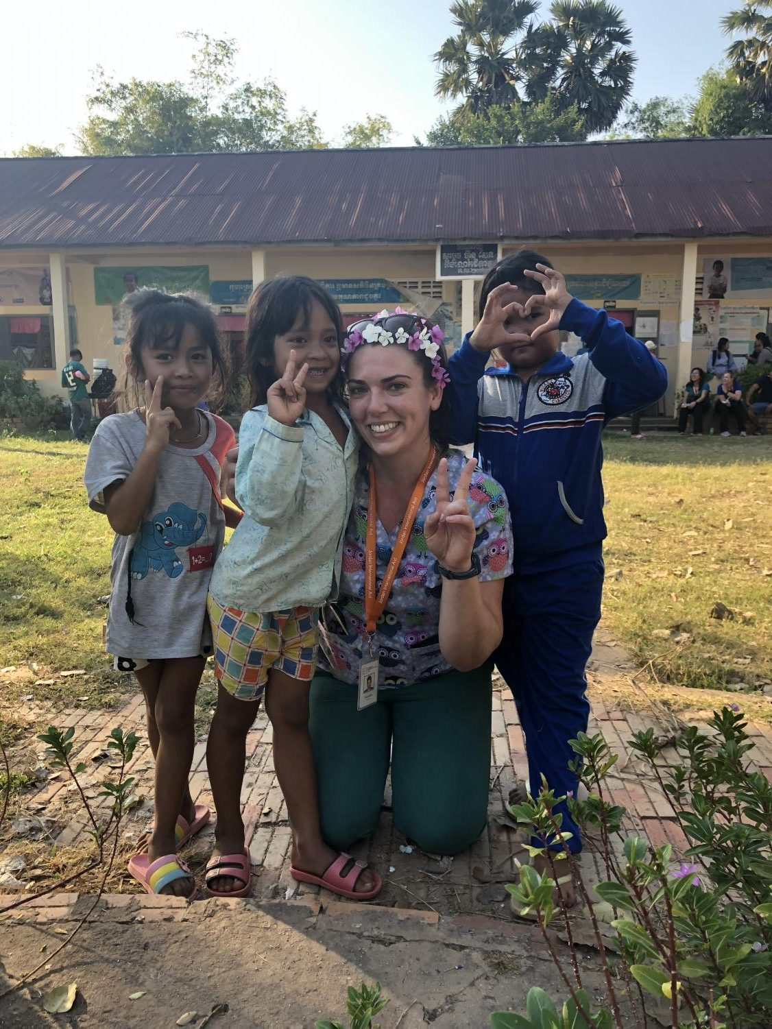 De Anza nursing graduate Emily Miller makes a peace sign and poses with kids.   Source: Emily Miller