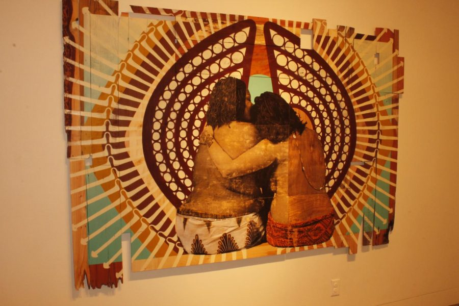"Jessica Sabogal and Shanna Strauss, ""The Invisible Labor of Women of Color,"" acrylic on found wood, depicts two queer women of color and size embracing."
