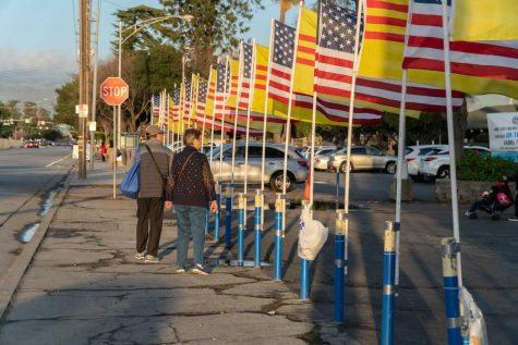 An old couple stands infront of the venue with the Vietnam and American flags
