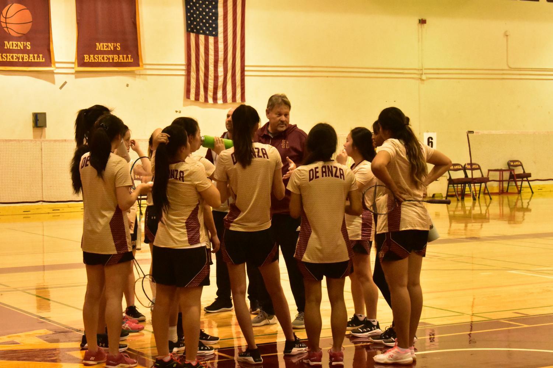 Women's badminton head coach Mark Landefeld talks with team.