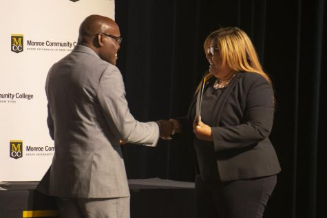 Lloyd Holmes presenting an award to a staff member during a staff appreciation ceremony at Monroe College.