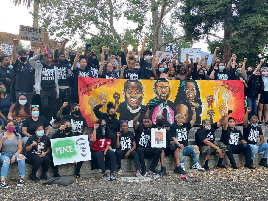 Black Lives Matter protesters raise their fists in solidarity with the movement June 9 in San Jose, and raise a poster with the faces of Breonna Taylor, George Floyd and Armand Abhari.