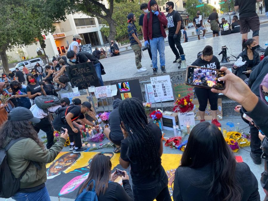 Protesters place candles, flowers and posters at a memorial for the Black victims who died at the hands of police brutality.