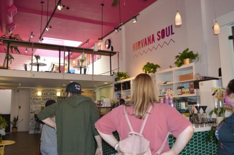 "Customers lined up behind a counter with the words ""Nirvana Soul"" on the wall."