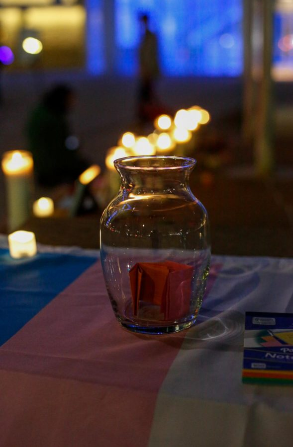 At the Transgender Day Of Remembrance vigil, participants write down their thoughts and wishes on a paper and put it into a glass jar.