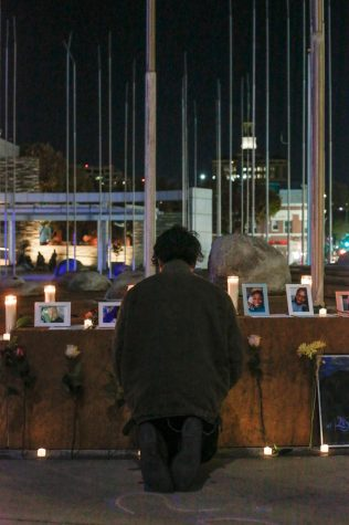 A participant kneels in front of the pictures of transgender victims and prays.