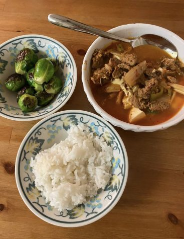 Kimchi soup, a Korean stew-like dish, partnered with a bowl of steamed rice and brussell sprouts.