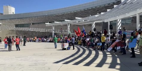 Various organizations sat down holding up their signs and flags on International Workers